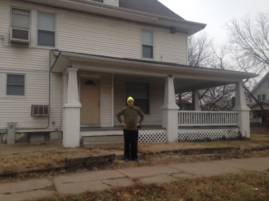 Man in running clothes standing in front of a house.