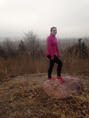 Girl in running clothes standing on a rock.