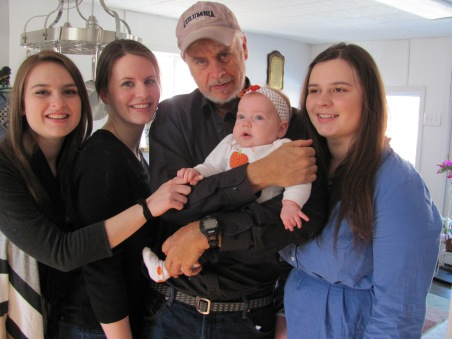Man holding bab with three young women.